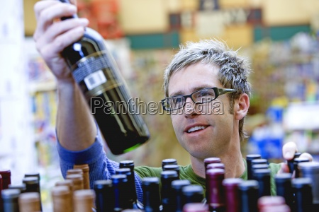 man shopping for wine in supermarket