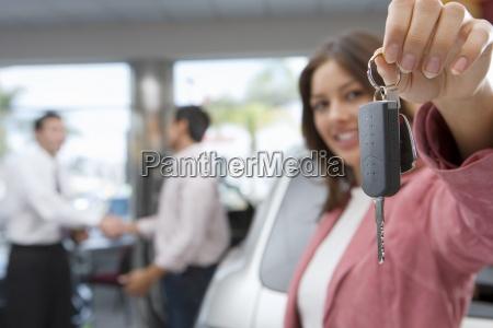 salesman haendeschuetteln mit kunden im autosalon