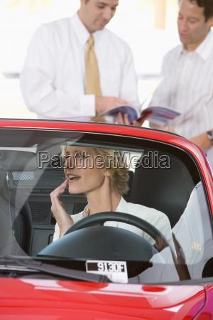 donna seduta in rosso convertibile nella