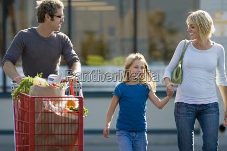 family leaving supermarket father pushing shopping