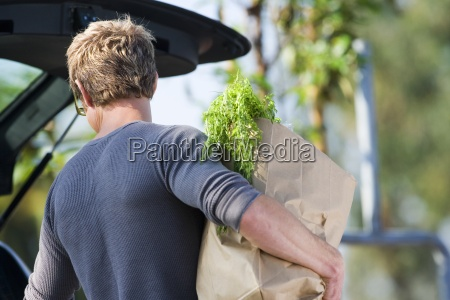 man loading groceries into car boot