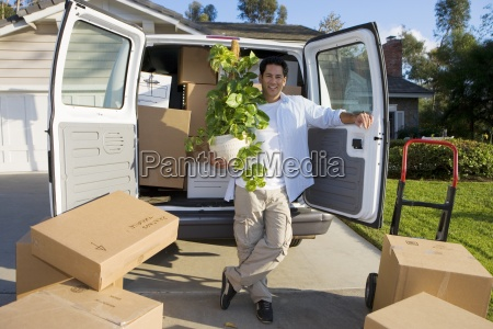 man moving house standing beside van