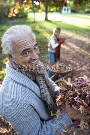 senior couple collecting autumn leaves in