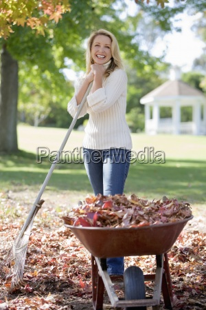 woman collecting autumn leaves in garden
