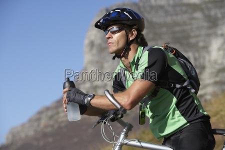 male, mountain, biker, sitting, on, bicycle, - 12975344