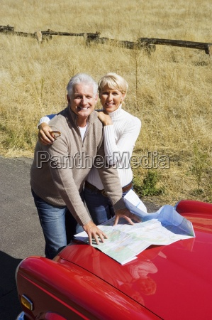 mature couple standing beside red car