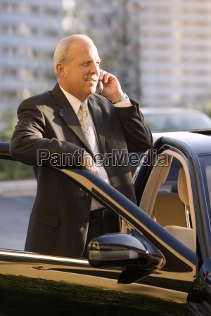 senior businessman standing beside stationary car