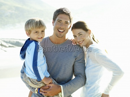 family standing on beach father carrying