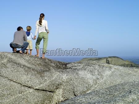 family standing on rock overlooking atlantic