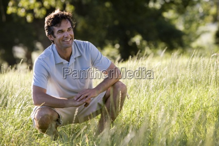 man crouching in woodland field smiling