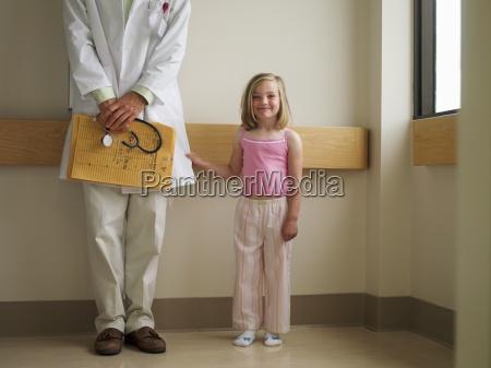 girl 6 8 standing beside doctor