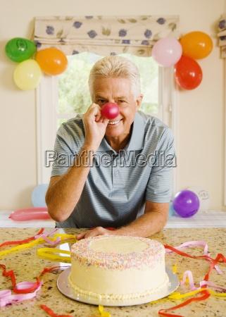 senior man sitting beside birthday cake