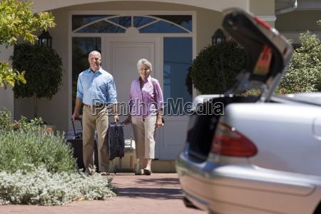 senior couple leaving house with luggage
