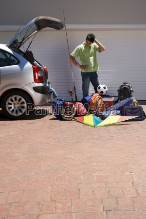 man loading camping equipment into parked