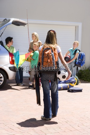 family loading camping equipment into parked