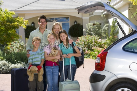 family standing with luggage beside open