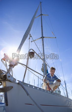man crouching on deck of moored