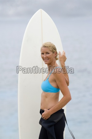 female surfer in wetsuit with surfboard