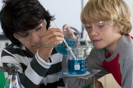 students performing experiment in school chemistry