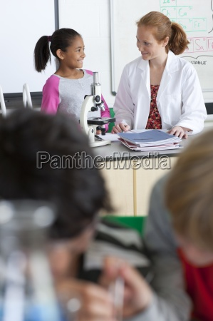 teacher helping student performing experiment in