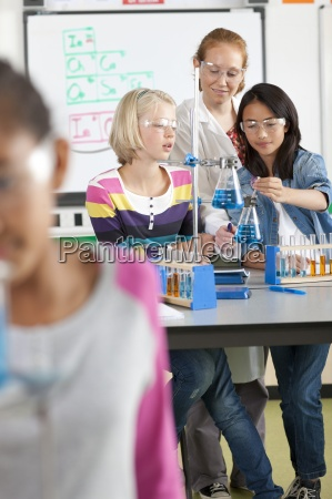 teacher helping students performing experiment in