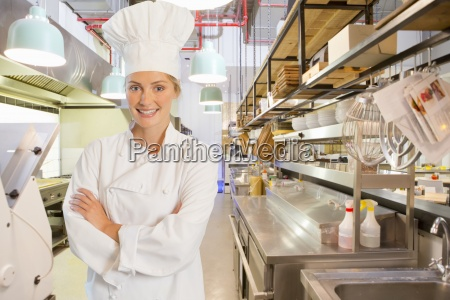 confident smiling chef standing with arms