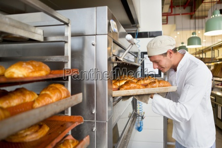 smiling baker checking tray of bread