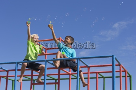 boys blowing bubbles with bubble wands