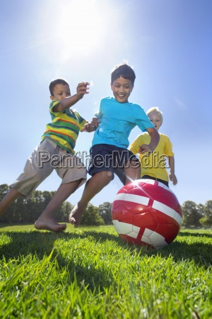 smiling boys playing soccer in park