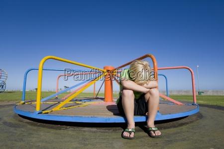 frustrated boy sitting on still merry