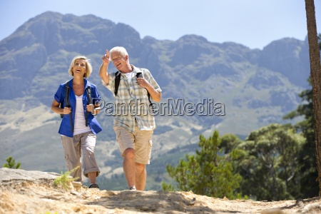 older couple hiking on rural hillside