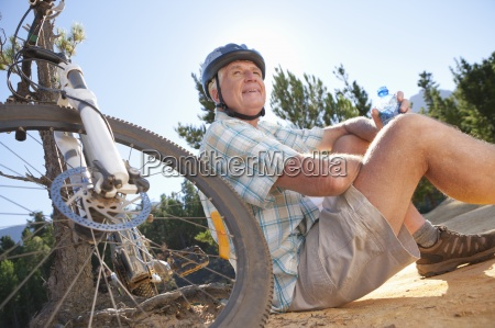 older man near mountain bike drinking