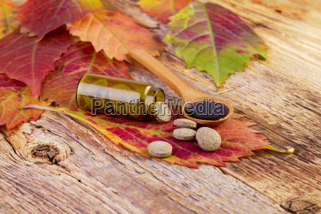 medicine bottle pills on leaf and