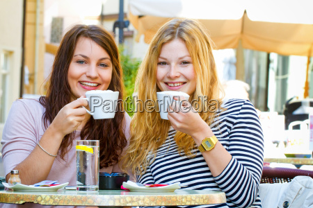 two young women in street cafe