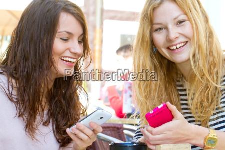 two girlfriends with mobile phone in