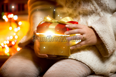 young woman opening gift box with
