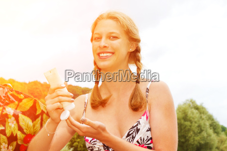 young woman applying the sunscreen