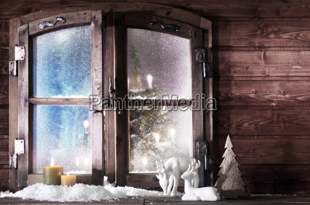 christmas decorations at wooden window pane