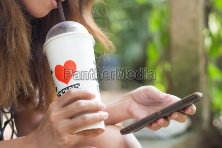 women drink ice coffee and use