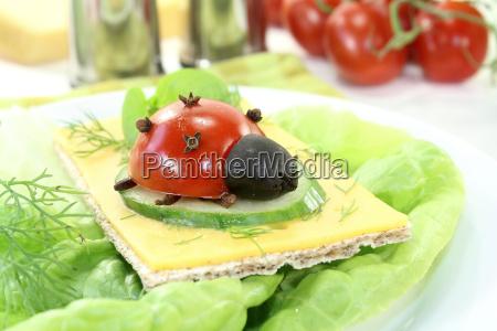 crispbread with cheese basil and ladybugs