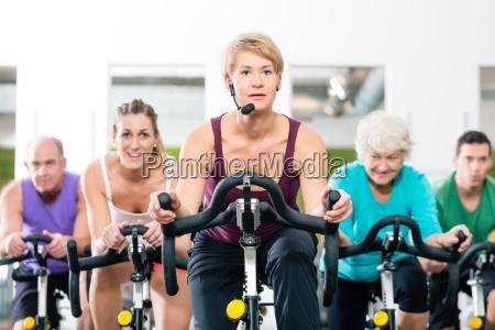 seniors at spinning on fitness bike