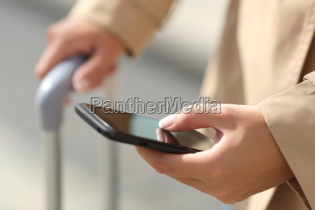 traveler woman hand consulting a smartphone