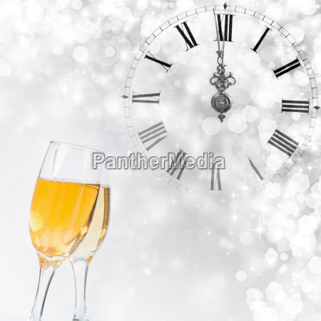 glasses with champagne and clock close