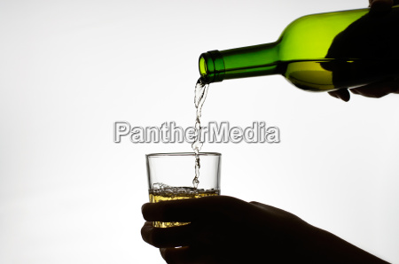 female hand pouring wine into glass