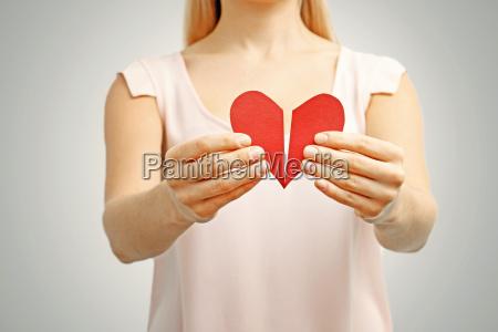 broken red heart in woman hands