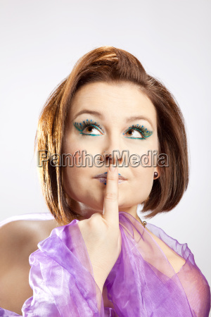 woman with index finger on mouth