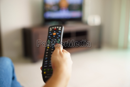 woman sitting watching tv changing channel