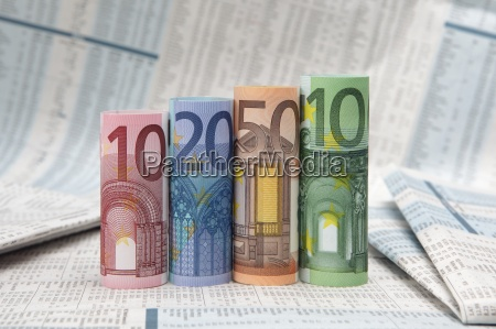 rolled up euro bills on financial