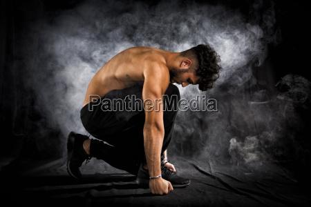 handsome shirtless muscular young man kneeling
