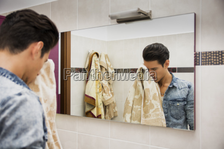 reflection of man drying face with